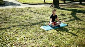 Yoga nella sosta Giovane in Lotus Position, sedentesi sull'erba verde Il concetto di pace e della meditazione prores, lenti stock footage