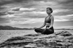 Yoga noir et blanc sur la roche au coucher du soleil Photo stock