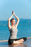Yoga By Ocean. An attractive young woman doing yoga on a jetty by the sea Stock Image