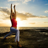 Yoga by the Ocean. Yoga woman practising her strength and balance Royalty Free Stock Images