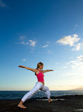 Yoga by the Ocean. Yoga woman practising her strength and balance Stock Photo