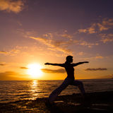 Yoga by the Ocean. Yoga woman poses at sunset Royalty Free Stock Images