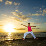 Yoga by the Ocean. Yoga woman poses at sunset stock photography