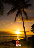 Yoga by the Ocean. Yoga wmen silhouette, working on poses at sunset stock images