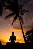 Yoga by the Ocean. Yoga woman silhouette, working on poses at sunset royalty free stock photo