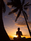 Yoga by the Ocean. Yoga woman silhouette, working on poses at sunset Royalty Free Stock Image