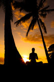 Yoga by the Ocean. Yoga woman silhouette, working on poses at sunset Royalty Free Stock Images