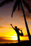 Yoga by the Ocean. Yoga woman poses at sunset Stock Image
