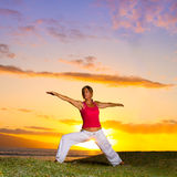 Yoga by the Ocean. Yoga woman poses at sunset Stock Photo