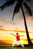 Yoga by the Ocean. Yoga woman poses at sunset stock photos