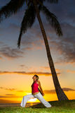 Yoga by the Ocean. Yoga woman poses at sunset Royalty Free Stock Photography