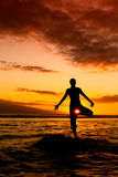 Yoga by the Ocean. Yoga wmen silhouette, working on poses at sunset stock photos