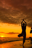 Yoga by the Ocean. Yoga woman silhouette, working on poses at sunset stock images