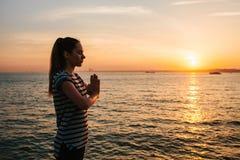 Yoga och meditation för ung härlig flicka praktiserande bredvid havet på solnedgången sport yoga meditation rekreation Royaltyfri Bild