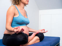 Yoga och meditationen för gravid kvinna göra sig till praktiserande i lotusblomma ( Royaltyfria Bilder