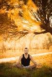 Yoga och sunt livsstilbegrepp Ståenden av mannen som mediterar i lätt sammanträde, poserar på gräs parkerar in Varm ljus signallj royaltyfri bild