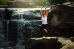 YOGA Old woman practicing yoga poses. On waterfall of natural Royalty Free Stock Photo