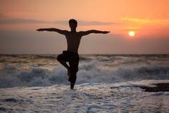 yoga ondulata di tramonto della siluetta del tirante della spiaggia Fotografie Stock