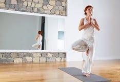 Yoga one leg balance Tree pose on wooden floor Royalty Free Stock Photos