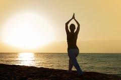 Yoga op het strand bij zonsopgang. Stock Foto's