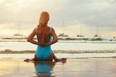 Yoga op het strand dichtbij het water in zonsondergang royalty-vrije stock fotografie