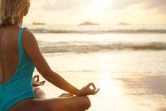 Yoga op het strand dichtbij het water in zonsondergang royalty-vrije stock afbeelding