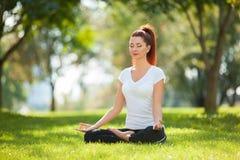 Yoga openlucht De gelukkige vrouw die yogaoefeningen doen, mediteert Stock Foto's