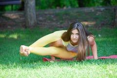 Yoga openlucht De gelukkige vrouw die yogaoefeningen doen, mediteert in het park Mooie vrouw het praktizeren yoga op het gras royalty-vrije stock afbeelding