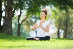 Yoga openlucht De gelukkige vrouw die yogaoefeningen doen, mediteert in het park Yogameditatie in aard Concept gezonde levensstij royalty-vrije stock foto's