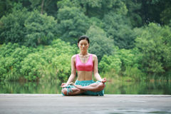 Yoga outdoor. A young chinese woman practicing yoga in the outdoors Royalty Free Stock Photos