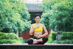 Yoga outdoor. A young chinese woman practicing yoga in the outdoors Stock Images