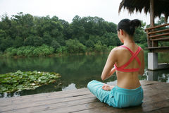 Yoga outdoor. A young chinese woman practicing yoga in the outdoors Stock Photos