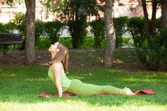 Yoga outdoor. Happy woman doing yoga exercises, meditate in the park. Pretty woman practicing yoga on the grass stock image