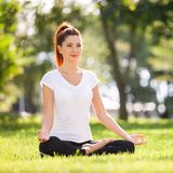 Yoga outdoor. Happy woman doing yoga exercises, meditate in the park. Yoga meditation in nature. Concept of healthy lifestyle stock images