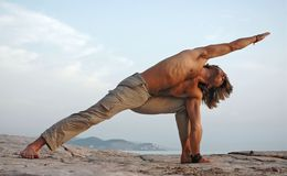 Yoga outdoors. Man doing yoga outdoors. Parshvakonasana. Side view Royalty Free Stock Image