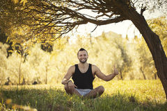 Yoga outdoors in warm autumn park. Sinlight effect. Man sits in Royalty Free Stock Photos