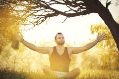 Yoga outdoors in warm autumn park. Sinlight effect. Man sits in Royalty Free Stock Images