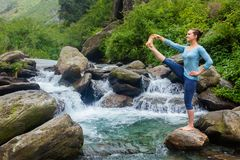 Woman doing Ashtanga Vinyasa Yoga asana outdoors at waterfall. Yoga outdoors - woman doing Ashtanga Vinyasa Yoga balance asana Utthita Hasta Padangushthasana stock photos