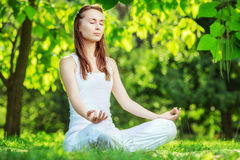 Yoga outdoors. Woman meditating in lotus position. Concept of he Stock Photos