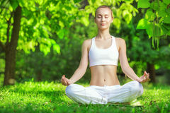 Yoga outdoors. Woman meditating in lotus position. Concept of he Stock Images
