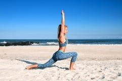 Yoga outdoors - woman practicing yoga at beach stock photo