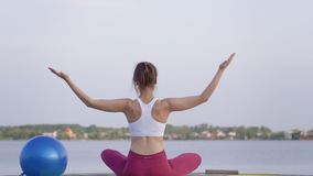 Yoga outdoors, young attractive yogi girl in lotus position meditates and enjoy spiritual calmnes on nature. Near water stock footage