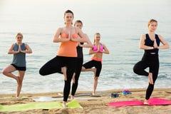 Yoga på havsstranden, grupp av unga kvinnor royaltyfri fotografi