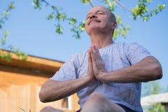 Yoga på parkerar Hög man med mustaschen med namastesammanträde Begrepp av stillhet och meditationen arkivfoton