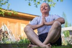 Yoga på parkerar Hög man med mustaschen med namastesammanträde Begrepp av stillhet och meditationen royaltyfri bild