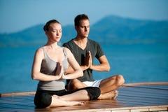 Yoga-Paare durch Ocean Lizenzfreie Stockfotografie