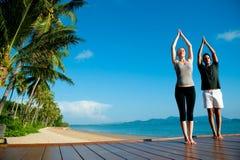 Yoga-Paare durch Ocean Stockbild
