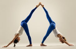 Yoga in pair. Balance. splits. leg high royalty free stock photo