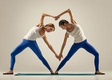 Yoga in pair. heart. Sporty yogi sisters doing fitness training. studio shot. pair, couple yoga Royalty Free Stock Photos
