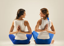Yoga in pair. stretching. back. seated Royalty Free Stock Photos